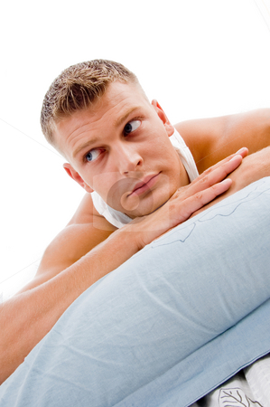 Man lying and looking sideways pillows stock photo, Man lying and looking sideways in bed against white background by Imagery Majestic