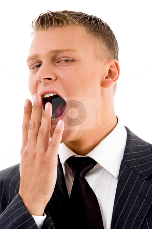Yawning young manager stock photo, Yawning young manager on an isolated background by Imagery Majestic