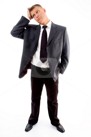 Standing young confused businessman stock photo, Standing young confused businessman against white background by Imagery Majestic