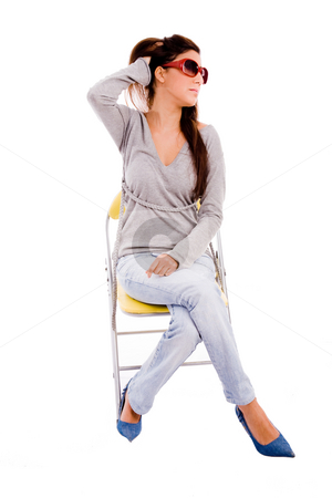 Front view of young model sitting on chair stock photo, Front view of young model sitting on chair on an isolated background by Imagery Majestic