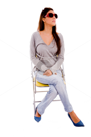 Front view of young female sitting on chair stock photo, Front view of young female sitting on chair against white background by Imagery Majestic