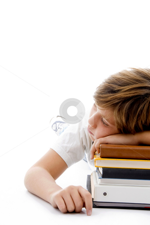 Half length view of boy sleeping on books stock photo, Half length view of boy sleeping on books on an isolated white background by Imagery Majestic