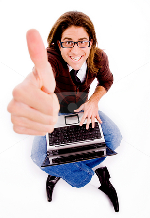 Top view of smiling man with thumbs up and laptop stock photo, Top view of smiling man with thumbs up and laptop on an isolated background by Imagery Majestic