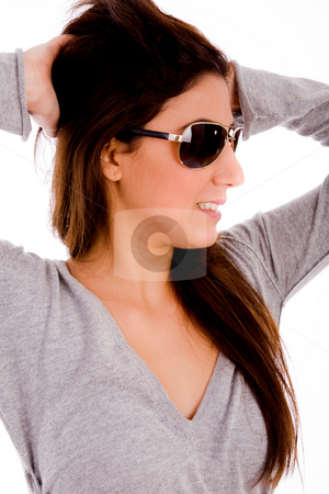 Smiling female with sunglasses holding her hair stock photo, Portrait of smiling female with sunglasses holding her hair on an isolated background by Imagery Majestic