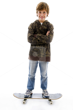 Front view of smiling boy standing on skateboard  stock photo, Front view of smiling boy standing on skateboard with white background by Imagery Majestic