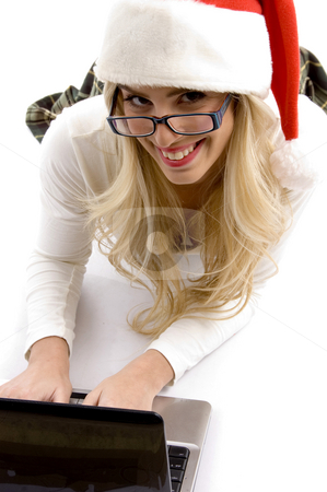 High angle view of woman in christmas hat working on laptop stock photo, High angle view of woman in christmas hat working on laptop on an isolated white background by Imagery Majestic