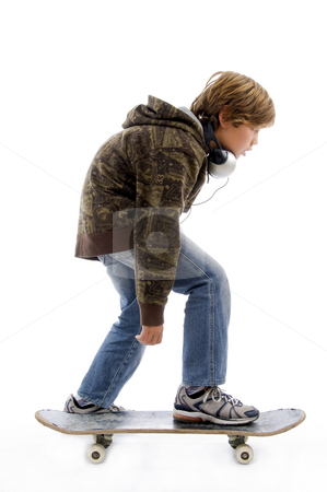 Urban teenager stock photo, Side pose of little boy riding skateboard against white background by Imagery Majestic