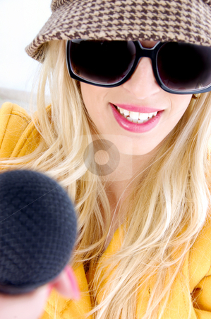 Smiling woman in sunglasses holding mic  stock photo, Front view of smiling woman in sunglasses holding mic by Imagery Majestic
