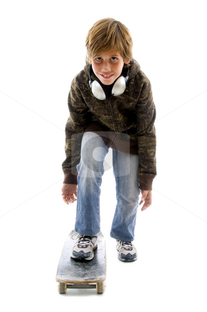 Urban teen on skateboard board stock photo, Front view of little boy riding skateboard on an isolated background by Imagery Majestic