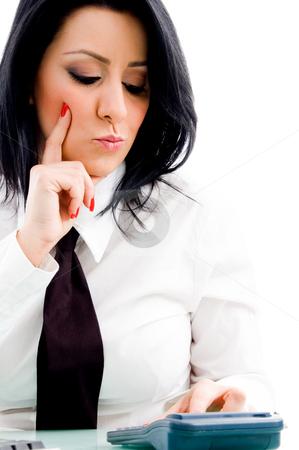 Woman operating calculator stock photo, Woman operating calculator with white background by Imagery Majestic
