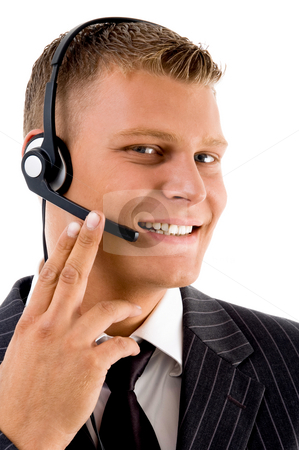 Young customer service operating with headset stock photo, Young customer service operating with headset against white background by Imagery Majestic