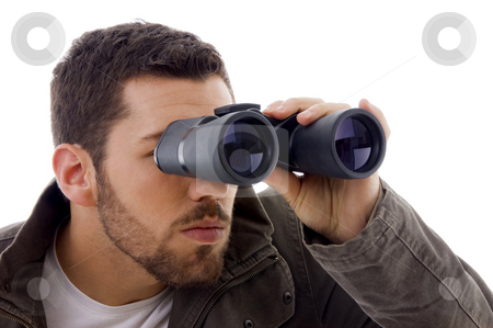 Side view of man looking through binoculars  stock photo, Side view of man looking through binoculars on an isolated background by Imagery Majestic