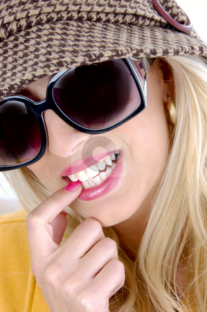 Front view of smiling female biting her finger stock photo, Front view of smiling female biting her finger by Imagery Majestic