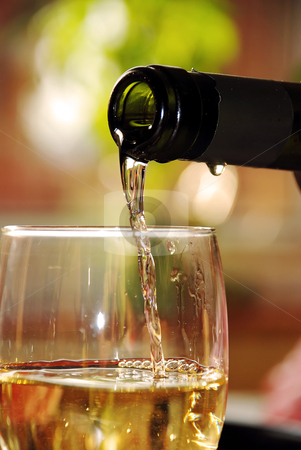 Glass of white wine stock photo, Pour wine from green bottle into glass by Julija Sapic