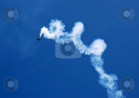 Acrobatic flight stock photo, Small plane in acrobatic flight with spiral trace over blue sky by Julija Sapic
