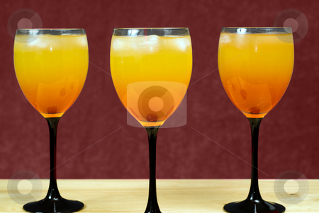 Alcohol Concept stock photo, Three alcoholic drinks mixed in wine glasses, sitting on a wooden counter by Richard Nelson