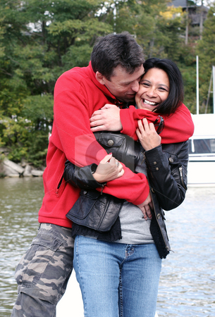 Couple in love stock photo, Couple hugging by the water by Christopher Meder