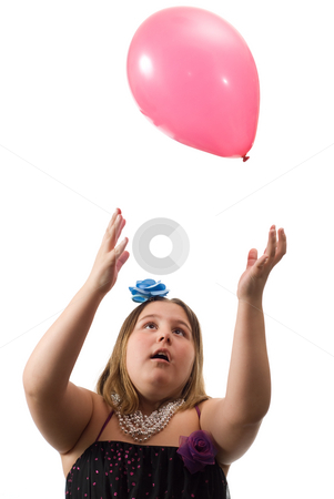 Girl Throwing Balloon stock photo, A young girl tossing a colored ballon up in the air and playing with it, isolated against a white background by Richard Nelson