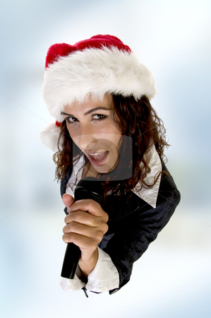Lady wearing christmas hat and singing into microphone stock photo, Lady wearing christmas hat and singing into microphone on an abstract  background by Imagery Majestic