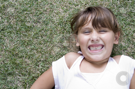 Laying girl with clenched teeth stock photo, Girl laying down on grass with clenched teeth by Imagery Majestic