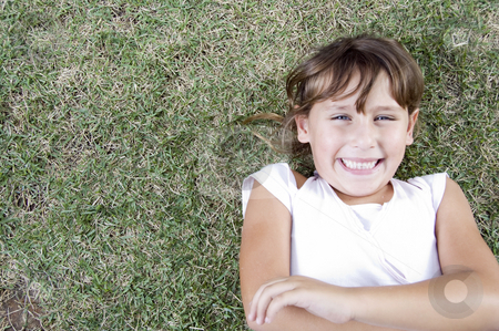Young cute girl lying on the grass stock photo, Smiling young cute girl lying on the grass by Imagery Majestic