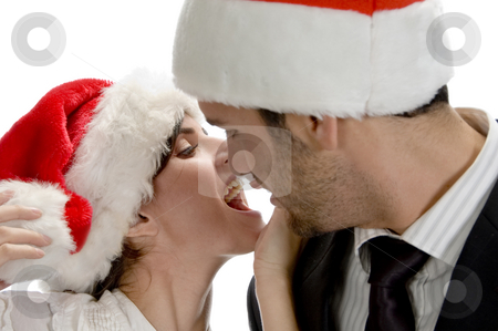 Couple kissing and wearing santa cap stock photo, Couple kissing and wearing santa cap against white background by Imagery Majestic
