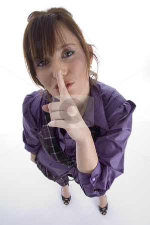 Woman instructing you to keep silent stock photo, Woman instructing you to keep silent against white background by Imagery Majestic