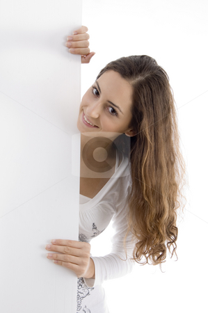 Young caucasian woman peeping over placard stock photo, Young caucasian woman peeping over placard against white background by Imagery Majestic