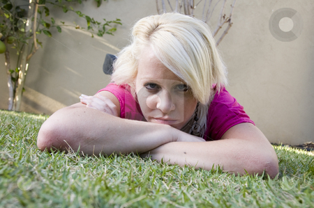 Caucasian female lying on the grass stock photo, Caucasian female lying on the grass in garden by Imagery Majestic