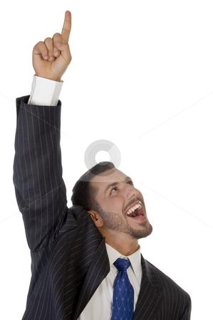 Happy businessman pointing upward stock photo, Happy businessman pointing upward on an isolated background by Imagery Majestic