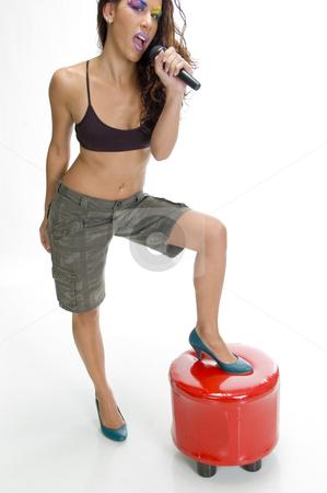 Singer putting leg on stool stock photo, Singer putting leg on stool against white background by Imagery Majestic