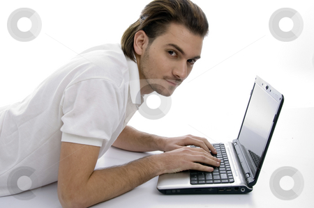 Young man with laptop stock photo, Young man with laptop on an isolated white backgound by Imagery Majestic