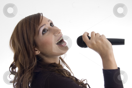 Woman singing in microphone stock photo, Woman singing in microphone on an isolated background by Imagery Majestic