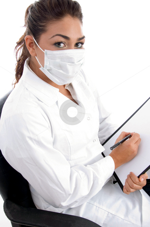 Sitting doctor with mask on her mouth and writing board stock photo, Sitting doctor with mask on her mouth and writing board against white background by Imagery Majestic