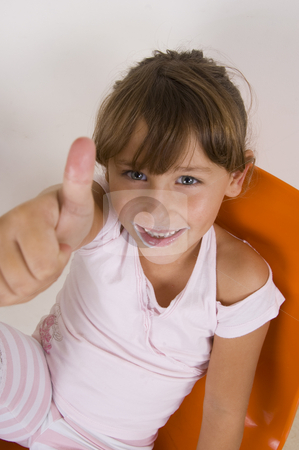 Smiling little girl showing thumb's up hand gesture stock photo, Smiling cute little girl showing thumb's up hand gesture by Imagery Majestic