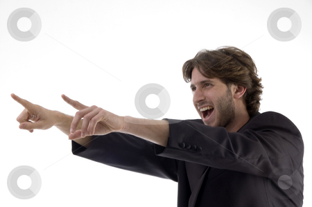 Shouting young man pointing sideways stock photo, Shouting young man pointing sideways against white background by Imagery Majestic