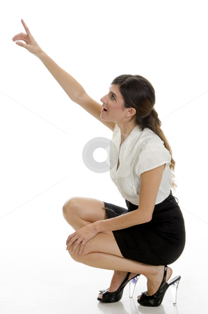 Sitting lady pointing upside stock photo, Sitting lady pointing upside against white background by Imagery Majestic
