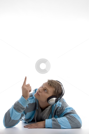 Laying young man with headphone pointing upward stock photo, Laying young man with headphone pointing upward on an isolated background by Imagery Majestic