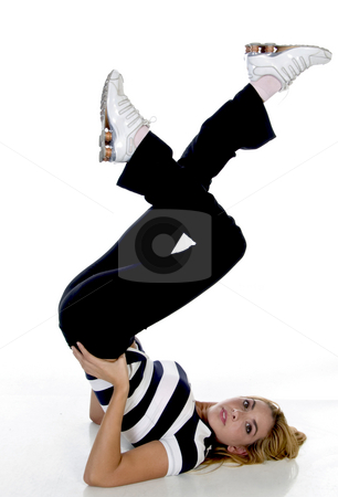 Female fitness trainer raising her legs stock photo, Female fitness trainer raising her legs on an isolated white background by Imagery Majestic