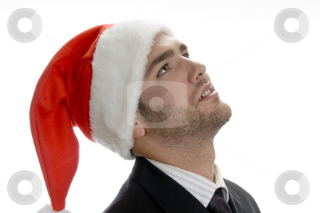 Young man looking upside stock photo, Young man looking upside and wearing santa cap by Imagery Majestic
