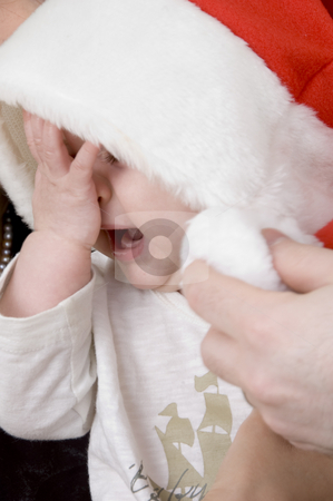 Crying baby with christmas hat stock photo, Crying small baby with christmas hat by Imagery Majestic