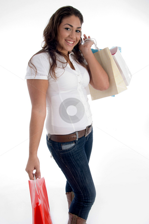 Happy girl posing with shopping bags stock photo, Happy girl posing with shopping bags on an isolated white background by Imagery Majestic