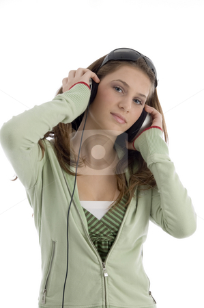 Pretty young woman listening to music stock photo, Pretty young woman listening to music against white background by Imagery Majestic