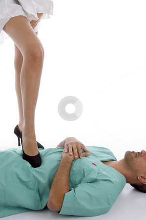 Patient keeping leg on doctor's chest stock photo, Patient keeping leg on doctor's chest on an isolated white background by Imagery Majestic