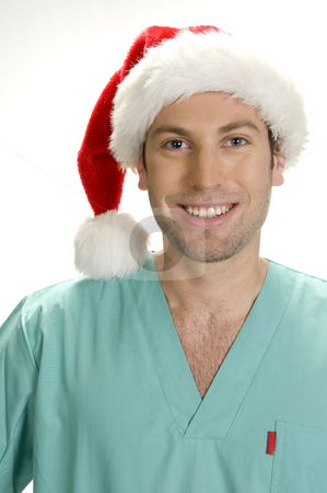 Posing handsome doctor with santa cap stock photo, Posing handsome doctor with santa cap by Imagery Majestic