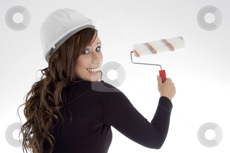 Woman with architect helmet and paint brush stock photo, Woman with architect helmet and paint brush against white background by Imagery Majestic