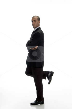 Young businessman standing on one leg stock photo, Young businessman standing on one leg with white background by Imagery Majestic