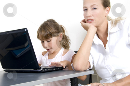 Mother and daughter working on laptop stock photo, Portrait of mother and daughter working on laptop by Imagery Majestic
