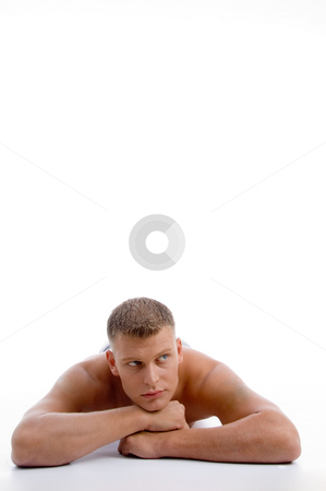 Laying muscular male looking aside stock photo, Laying muscular male looking aside on an isolated background by Imagery Majestic
