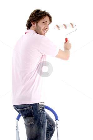 Man standing on chair and holding paint roller stock photo, Man standing on chair and holding paint roller on an isolated white background by Imagery Majestic